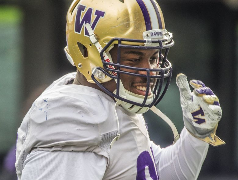 University of Washington DL Levi Onwuzurike smiling after hitting the sled during the start of Spring football practice at Husky Stadium in 2019.    (Steve Ringman / The Seattle Times)