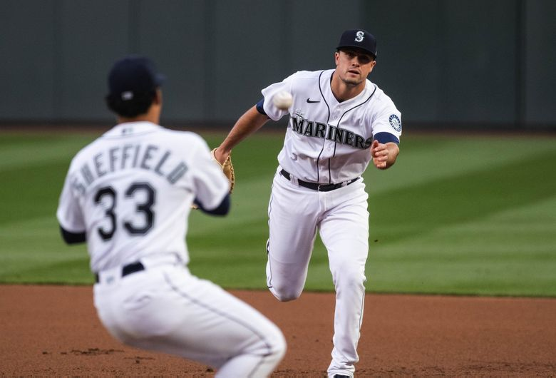 Evan White flips the ball to pitcher Justus Sheffield who's covering first to make the put out of LA's Zach McKinstry to end the sides in the 2nd.  The Los Angeles Dodgers played the Seattle Mariners Monday, April 19, 2021 at T-Mobile Park in Seattle, WA. (Dean Rutz / The Seattle Times)