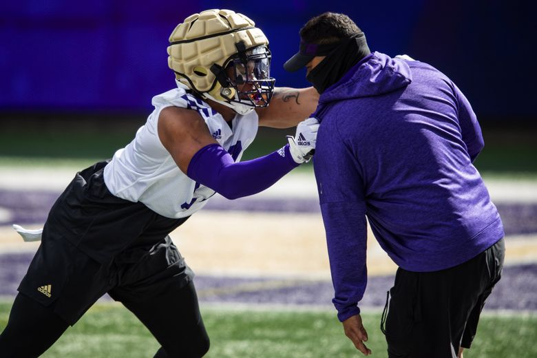 Outside linebacker Sav'ell Smalls practices tackling drills with Ikaika Malloe, co-defensive coordinator and outside linebackers coach, as the University of Washington Huskies participate in their spring practice at Husky Stadium Saturday April 10, 2021 in Seattle. (Bettina Hansen / The Seattle Times)