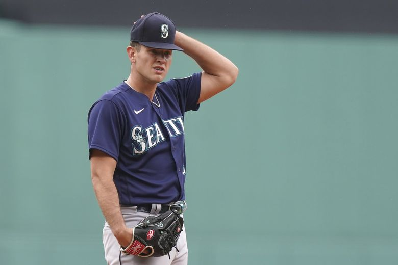 Seattle Mariners' Nick Margevicius adjusts his hat on the mound after allowing the Boston Red Sox to score runs on walks in the first inning Sunday. (Steven Senne / The Associated Press)