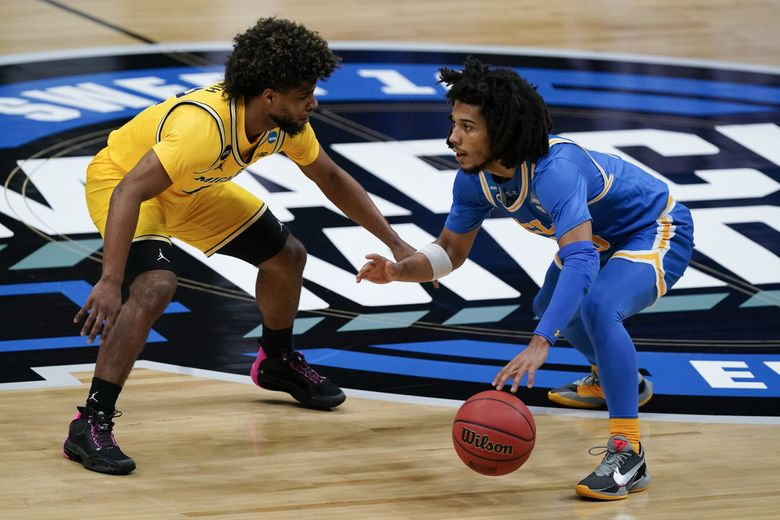 UCLA guard Tyger Campbell, right, drives past Michigan guard Mike Smith, left, during the first half of an Elite 8 game in the NCAA men's college basketball tournament at Lucas Oil Stadium, Tuesday, March 30, 2021, in Indianapolis. (Michael Conroy / The Associated Press)