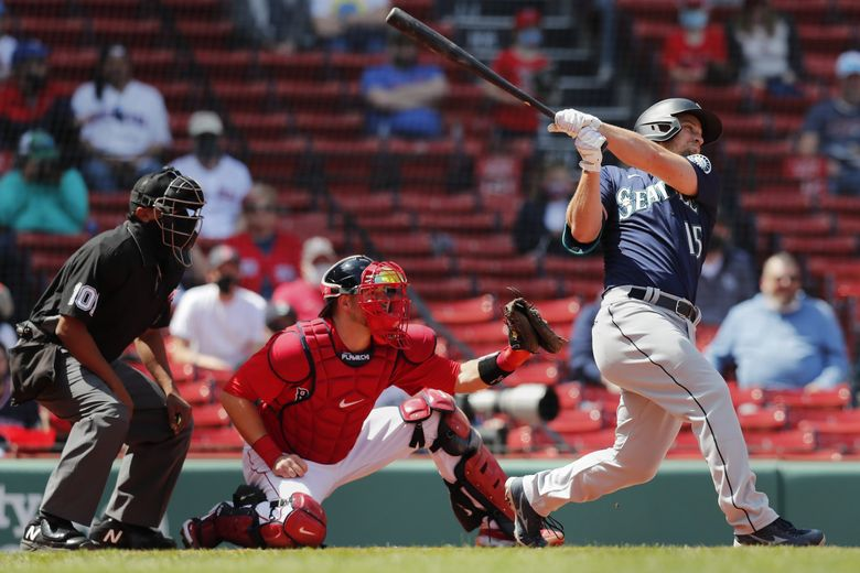 The Mariners' Kyle Seager follows through on his two-run triple in front of Boston Red Sox's Kevin Plawecki during the second inning Saturday. (Michael Dwyer / The Associated Press)