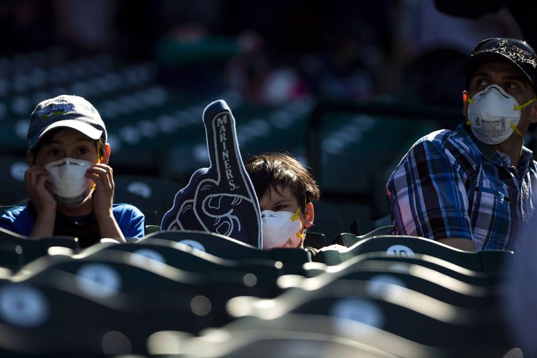 From left, brothers Lucas Moncivaiz, left, and Daniel Moncivaiz, with their father Edward Moncivaiz, right, cheer on the Mariners in the ninth inning in a game against Los Angeles Dodgers at T-Mobile Park on Thursday, April 20, 2021. (Amanda Snyder / The Seattle Times)