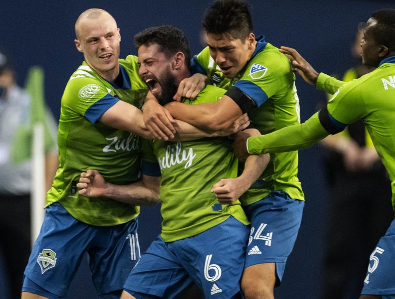 The Sounders gather around Joao Paulo following his second-half goal Friday.  Minnesota United FC played the Seattle Sounders FC in their MLS season opener Friday, April 16, 2021 at Lumen Field in Seattle. (Dean Rutz / The Seattle Times)