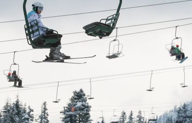 A skier rides the lift up a line at The Summit at Snoqualmie Pass on Christmas Day, Dec. 25, 2019.