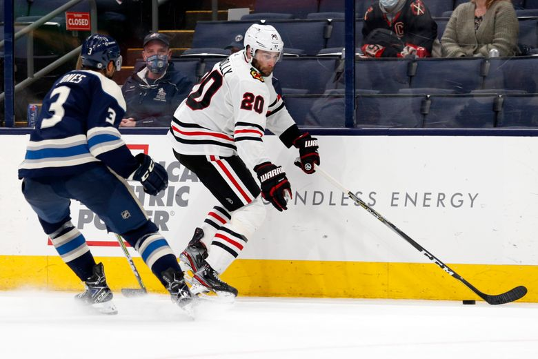 Chicago Blackhawks forward Brett Connolly, right, controls the puck in front of Columbus Blue Jackets defenseman Seth Jones during the third period of an NHL hockey game in Columbus, Ohio, Monday, April 12, 2021. (AP Photo/Paul Vernon)