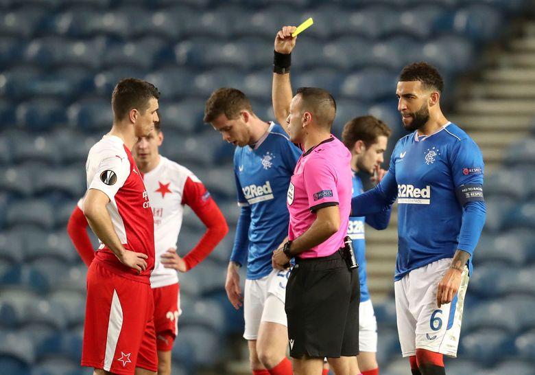 Slavia Prague's Ondrej Kudela, left, receives a yellow card during the UEFA Europa League Round of Sixteen soccer match at Ibrox Stadium, Glasgow, Thursday March 18, 2021. (Andrew Milligan/PA via AP)