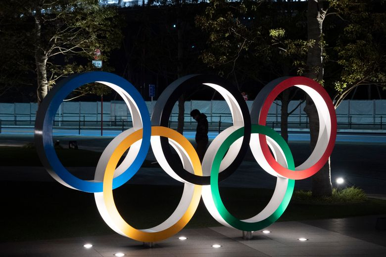 """FILE – In this March 24, 2020, file photo, a man is seen through the Olympic rings installed near the National Stadium in Tokyo. Athletes at the Tokyo Olympics who come down with minor symptoms of COVID-19 could be isolated in a hotel lined up by local organizers of the games. Japan's Kyodo news agency cited unnamed officials with """"knowledge of the plan."""" The Japanese news agency on Sunday, April 11, 2021, said organizers are working to secure 300 rooms in a hotel near the Athletes Village. (AP Photo/Jae C. Hong, File)"""