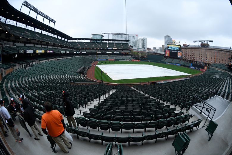 Tarp lays on the infield while the scoreboard signals the postponement of game three between the Baltimore Orioles and the Seattle Mariners due to weather, Wednesday, April 14, 2021, in Baltimore. The game will be played as a doubleheader Thursday, April 15. (Nick Wass / AP)