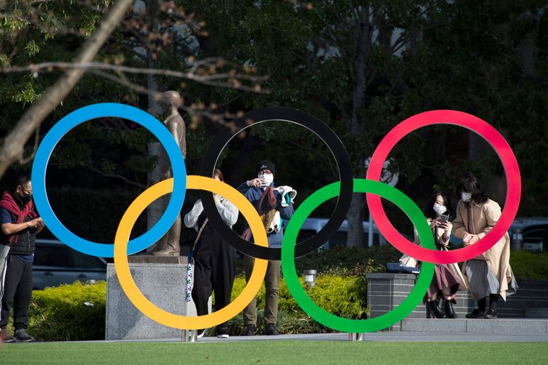 FILE – In this March 19, 2021, file photo, people take pictures of the Olympic rings installed by the Japan Olympic Museum in Tokyo. The vaccine rollout in Japan has been very slow with less than 1% vaccinated. This of course is spilling over to concerns about the postponed Tokyo Olympics that open in just over three months.(AP Photo/Hiro Komae, File)