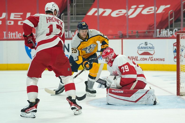 Detroit Red Wings goaltender Thomas Greiss (29) stops a Nashville Predators right wing Mathieu Olivier (25) shot as Filip Hronek (17) defends in the first period of an NHL hockey game Tuesday, April 6, 2021, in Detroit. (AP Photo/Paul Sancya)