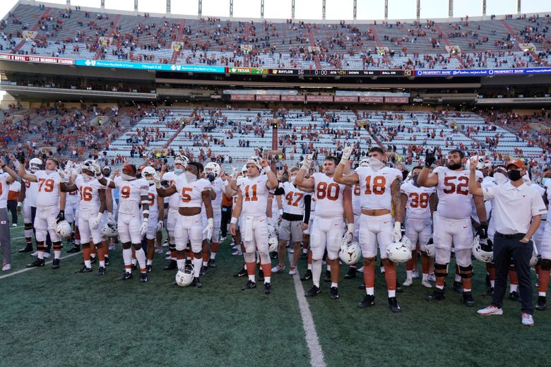 """FILE – In this Saturday, Oct. 24, 2020, file photo, Texas players, including Sam Ehlinger (11), sing """"The Eyes Of Texas"""" after an NCAA college football game against Baylor in Austin, Texas. The University of Texas marching band and pep band will be required to play """"The Eyes of Texas"""" school song when they return to performing, but the school will also create a new band that doesn't include it in its play list, the school has announced. The song has been mired in controversy since summer 2020 when a group of athletes and students called on the school to ditch the tune amid national racial injustice protests after the killing of George Floyd. (AP Photo/Chuck Burton, File)"""