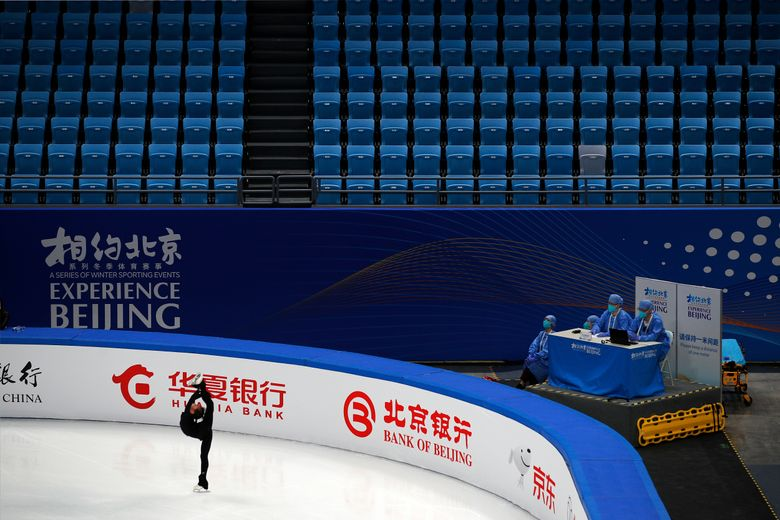 Medical workers wearing face masks and protective gears watch a Chinese figure skater perform her routine at the Capital Indoor Stadium during a test event for the 2022 Beijing Winter Olympics in Beijing, Friday, April 2, 2021. The organizers of the 2022 Beijing Winter Olympics has started 10 days of testing for several sport events in five different indoor venues from April 1-10, becomes the first city to hold both the Winter and Summer Olympics. (AP Photo/Andy Wong)