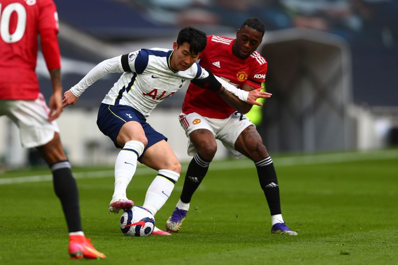Tottenham's Son Heung-min, left, is challenged by Manchester United's Aaron Wan-Bissaka during the English Premier League soccer match between Tottenham Hotspur and Manchester United at the Tottenham Hotspur Stadium in London, Sunday, April 11, 2021. (Clive Rose/Pool via AP)