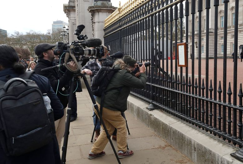 FILE – In this Friday, April 9, 2021 file photo, members of the media take images of an announcement, regarding the death of Britain's Prince Philip, displayed on the fence of Buckingham Palace in London. When Prince Philip's death was announced, the BBC switched instantly into mourning mode. Regular programming on the U.K.'s national broadcaster was canceled for special coverage, hosted by black-clad news anchors. Some Britons felt it a fitting mark of respect, but for others it was a bit much. (AP Photo/Matt Dunham, File)
