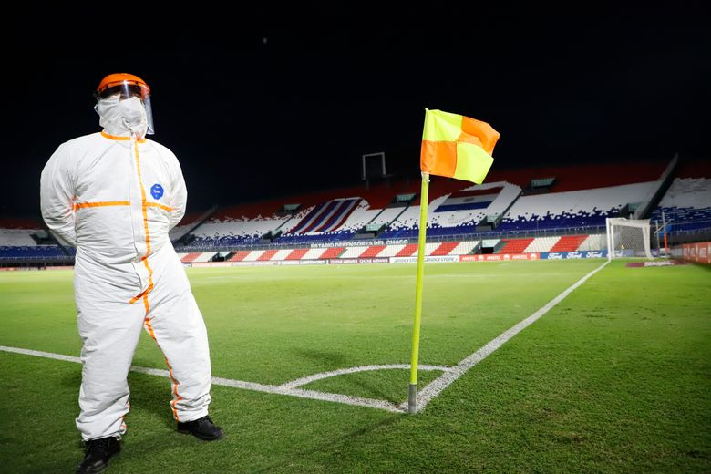 """A Conmebol worker, wearing protective gear due to COVID-19, stands guard on the pitch inside """"Defensores del Chaco"""" Stadium before the start of a Copa Libertadores soccer match between Brazil's Gremio and Ecuador's Independiente del Valle in Asuncion, Paraguay, Friday, April 9, 2021. (Natalia Aguilar/Pool via AP)"""