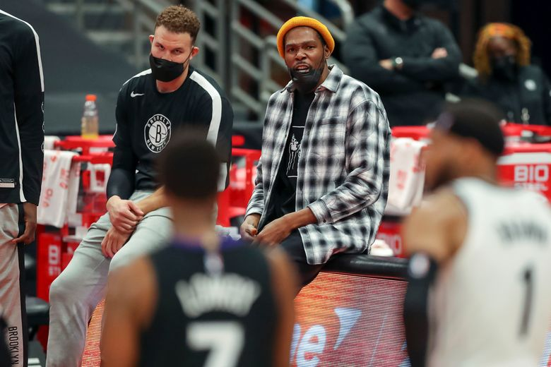 Brooklyn Nets' Kevin Durant, center, sits with Brooklyn Nets' Blake Griffin, left, during the second half of an NBA basketball game against the Toronto Raptors Wednesday, April 21, 2021, in Tampa, Fla. The Raptors won 114-103. (AP Photo/Mike Carlson)
