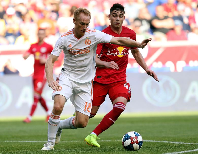 FILE – In this May 19, 2019, file photo, Atlanta United midfielder Jeff Larentowicz, left, keeps the ball away from New York Red Bulls forward Brian White during the first half of an MLS soccer match in Harrison, N.J. Larentowicz has retired after a 16-year career in Major League Soccer that included more than 400 appearances and championships in Colorado and Atlanta. (AP Photo/Steve Luciano, File)