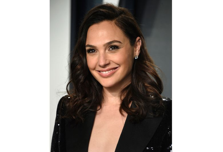 """FILE – Gal Gadot arrives at the Vanity Fair Oscar Party on Sunday, Feb. 9, 2020, in Beverly Hills, Calif.  Gadot is using her Hollywood star power to spotlight remarkable women from around the world. The """"Wonder Woman"""" actor is host and executive producer of a new documentary series """"National Geographic Presents IMPACT with Gal Gadot,"""" premiering Monday, April 26. (Photo by Evan Agostini/Invision/AP, File)"""