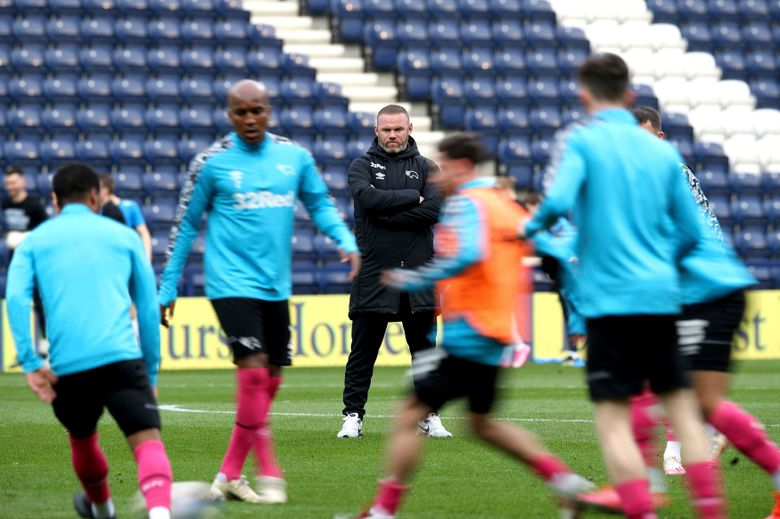 FILE – In this Tuesday, April 20, 2021 file photo, Derby County manager Wayne Rooney, centre back, watches his players warm up on the pitch ahead of their Championship soccer match against Preston at Deepdale Stadium, Preston, England.  Rooney the player found ways to score. Wayne Rooney the manager has hit a wall. The Manchester United great finds himself in a relegation battle in England's second division as Derby's losses pile up. The club that Rooney took over first on an interim basis as player-coach and then permanently in January upon his retirement has just one win from its past 13 games. (Martin Rickett/PA via AP, File)