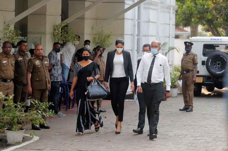 Mrs. World 2019 Caroline Jurie, center, leaves a police station after obtaining bail in Colombo, Sri Lanka, on Thursday. Jurie's decision to remove the crown from the the winning Mrs. Sri Lanka contestant on stage moments after the winner was announced, because of claims she was a divorcee, drew widespread social media condemnation.  he winner Pushpika de Silva who was crowned again later had complained to police that her head was wounded when the clips of her crown were removed by Jurie. (AP Photo/Eranga Jayawardena)