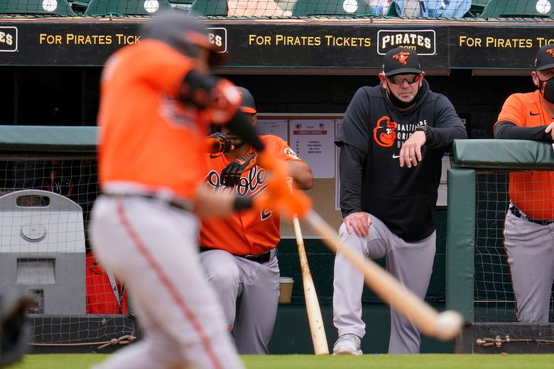 Baltimore Orioles manager Brandon Hyde, right, stands in the dugout steps as Yolmer Sanchez bats during the fourth inning of a spring training exhibition baseball game against the Pittsburgh Pirates in Bradenton, Fla., Monday, March 22, 2021. (AP Photo/Gene J. Puskar)