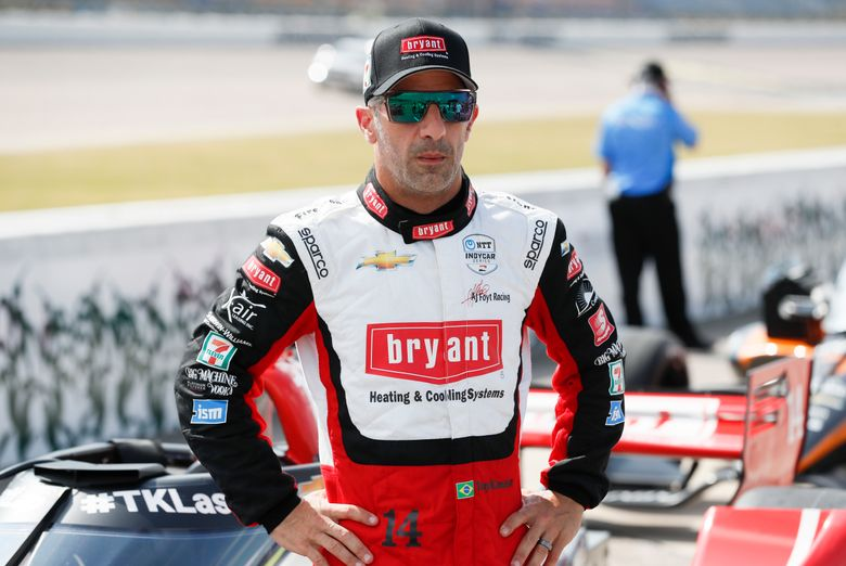 FILE – In this July 17, 2020, file photo, driver Tony Kanaan, of Brazil, stands next to his car during qualifying for an IndyCar Series auto race at Iowa Speedway in Newton, Iowa. Kanaan's supposed farewell tour last year fizzled amid nearly empty tracks. Then he was given another chance to extend his IndyCar career, this time before fans. His first two races come this weekend at Texas Motor Speedway. (AP Photo/Charlie Neibergall, File)