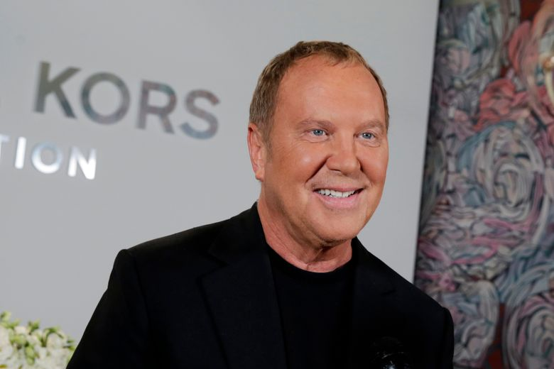 FILE – Designer Michael Kors appears before his Spring 2017 collection is modeled during Fashion Week, in New York, on Sept. 14, 2016. Kors loves fashion, but he also loves the Broadway theater. He celebrated that love as he marked his 40th anniversary as a designer this week, with a show that showcased the razzle-dazzle of Broadway. His models sashayed down a runway that was actually West 45th street, in the heart of Manhattan's still-shuttered theater district. (AP Photo/Richard Drew, File)