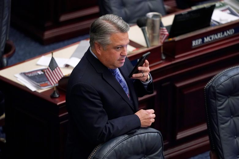 Florida Rep. Chip LaMarca talks on his phone during a break in a legislative session, Thursday, April 29, 2021, at the Capitol in Tallahassee, Fla. (AP Photo/Wilfredo Lee)