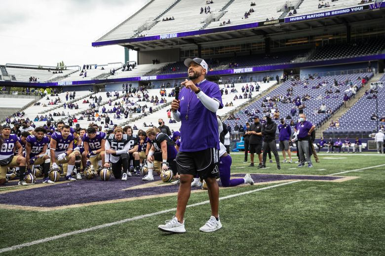 While his team takes a knee, Jimmy Lake addresses the fans at Husky Stadium for Saturday's spring game.  It was played before about 9,000 people Saturday, May 1, 2021 at Husky Stadium in Seattle, WA. 217000 (Dean Rutz / The Seattle Times)