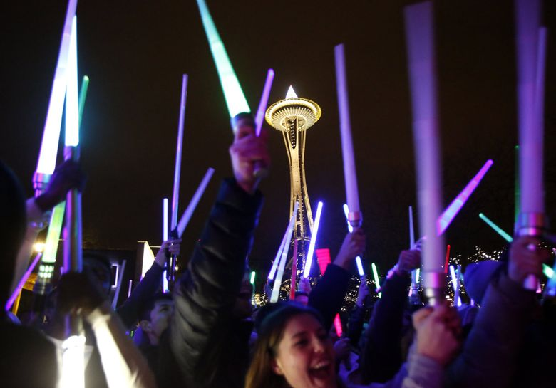 """""""Star Wars"""" fans waged a lightsaber battle in the shadow of the Space Needle to celebrate the opening of """"Star Wars: The Force Awakens"""" in 2015. (Sy Bean / The Seattle Times, file)"""
