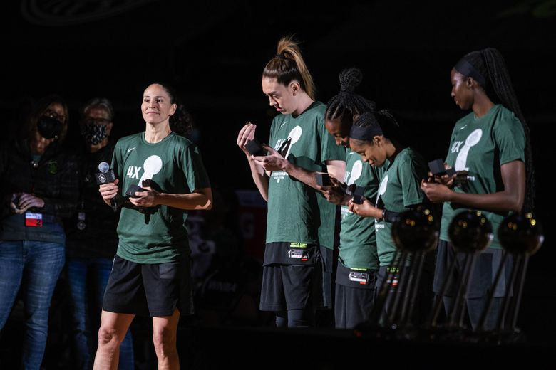 Storm players look at their championship rings during Saturday's ring ceremony before their opener against the Aces at Angel of the Winds Arena in Everett. (Dean Rutz / The Seattle Times)