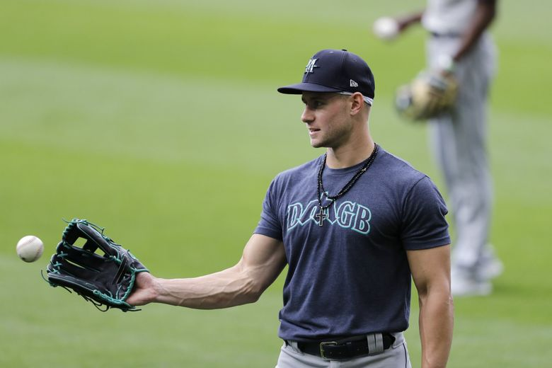 Seattle Mariners Jarred Kelenic reaches for a ball during a baseball practice Wednesday, July 22, 2020, in Seattle. (Elaine Thompson / AP)