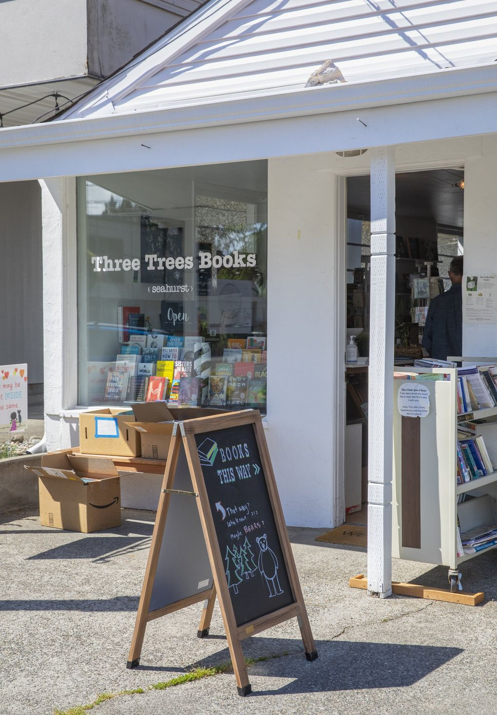 At Three Trees Books indie bookstore in Burien, people drop off puzzles and books that are free for any passerby who wants them. (Ellen M. Banner / The Seattle Times)