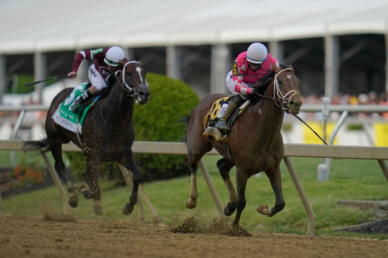 Flavien Prat atop Rombauer, right, breaks away from Irad Ortiz Jr. atop Midnight Bourbon moments before crossing the finish line to win the Preakness Stakes horse race at Pimlico Race Course, Saturday, May 15, 2021, in Baltimore. (AP Photo/Julio Cortez)