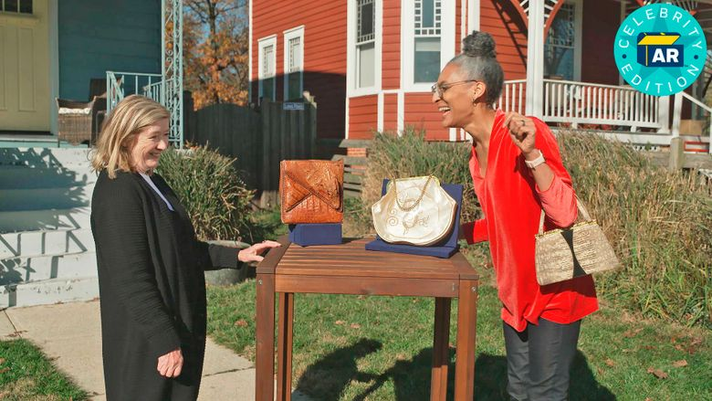 """This image released by WGBH-TV shows Katy Kane, left, as she appraises celebrity chefCarla Hall's vintage purse collection in an episode of """"Antiques Roadshow Celebrity Edition,"""" airing May 10 on PBS. (WGBH/PBS via AP)"""