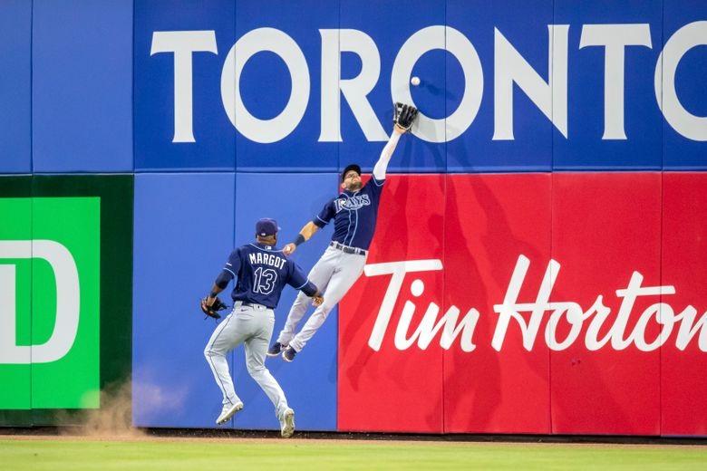 Tampa Bay Rays center fielder Kevin Kiermaier cannot catch as fly ball by Toronto Blue Jays' Marcus Semien as Manuel Margot covers during the second inning of a baseball game Friday, May 21, 2021, in Dunedin, Fla. (AP Photo/Mike Carlson)