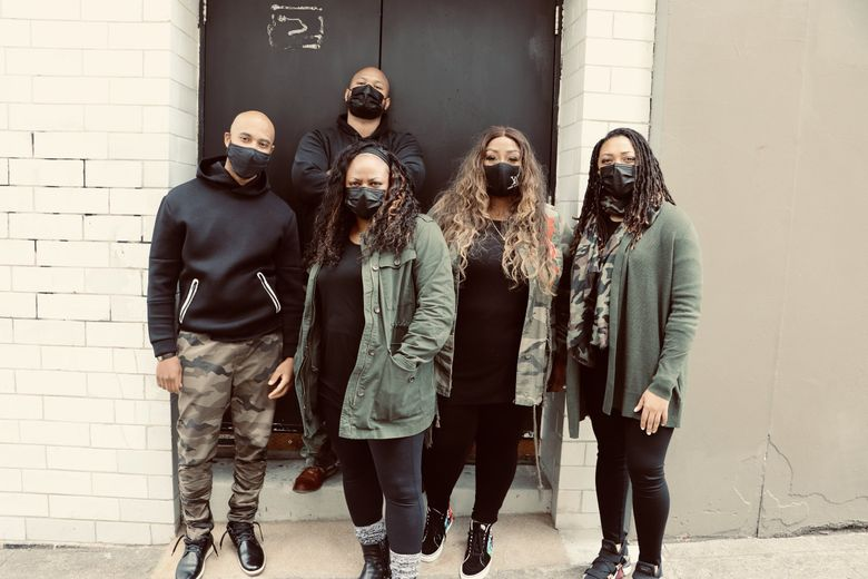 ELEVATE mentors, from left, Aaron Reader, Kyle Danielson, Shakiah Danielson, Tia-Nache Yarbrough and Nakeya Isabell stand in front of the Moore Theatre door on Virginia Street that was once used as a segregated entrance.  (Courtesy Seattle Theatre Group)