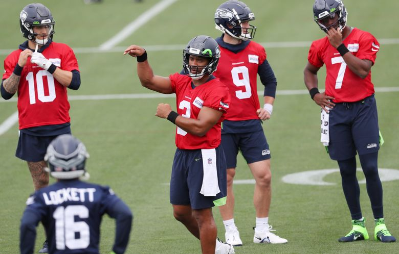 Quarterback Russell Wilson (3) talks with wide receiver Tyler Lockett (16) during Seahawks minicamp on Tuesday. (Ken Lambert / The Seattle Times)