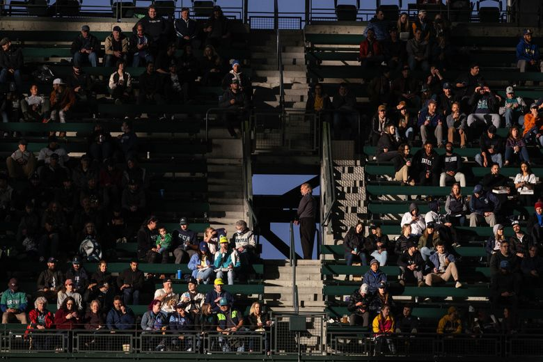 Despite the roof being closed, a ray of sunlight peeks beneath the T-Mobile Park roof and bathes fans in center field May 27. (Dean Rutz / The Seattle Times)