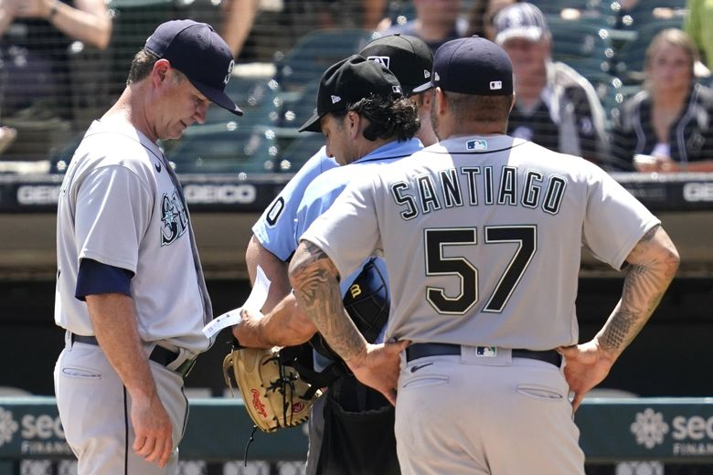 Seattle Mariners manager Scott Servais, left, listens to home plate umpire Phil Cuzzi about relief pitcher Hector Santiago, right, during the fifth inning in the first baseball game of a doubleheader against the Chicago White Sox in Chicago, Sunday, June 27, 2021. (Nam Y. Huh / The Associated Press)