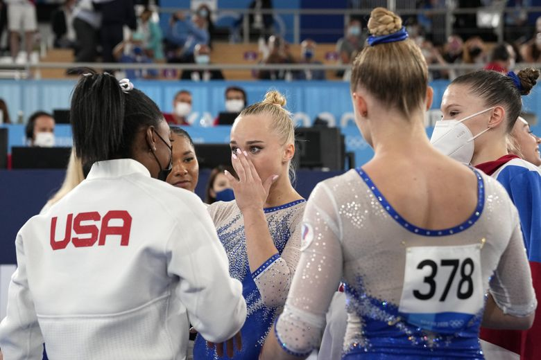 Simone Biles, of the United States, congratulates gymnasts from the Russian Olympic Committee's Liliia Akhaimova, back to camera, Vladislava Urazova, right, and Angelina Melnikova after they won the gold medal at the 2020 Summer Olympics, Tuesday, July 27, 2021, in Tokyo.(Ashley Landis / AP)