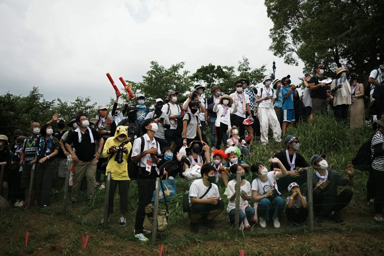 Masked fans watch from a hillside during the men's cross country mountain bike competition at the 2020 Summer Olympics, Monday, July 26, 2021, in Izu, Japan. (Thibault Camus / AP)