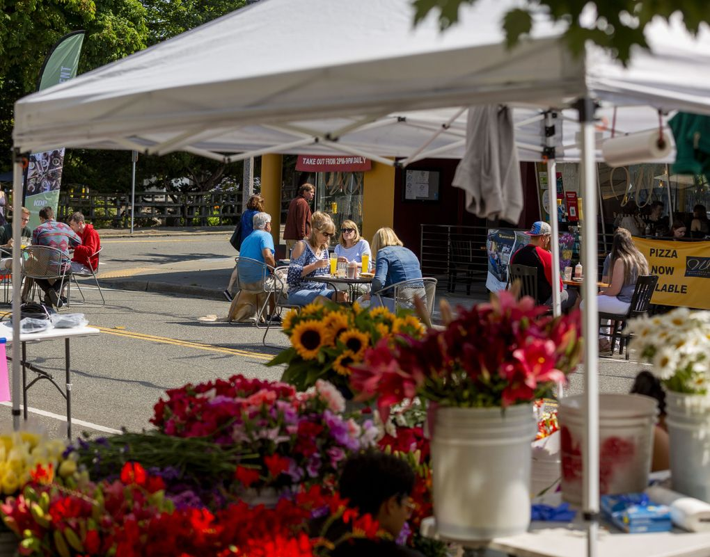 People dine outdoors at Inside OUT Open Air Dining & Marketplace on July 10 in Kent. (Sylvia Jarrus / The Seattle Times)