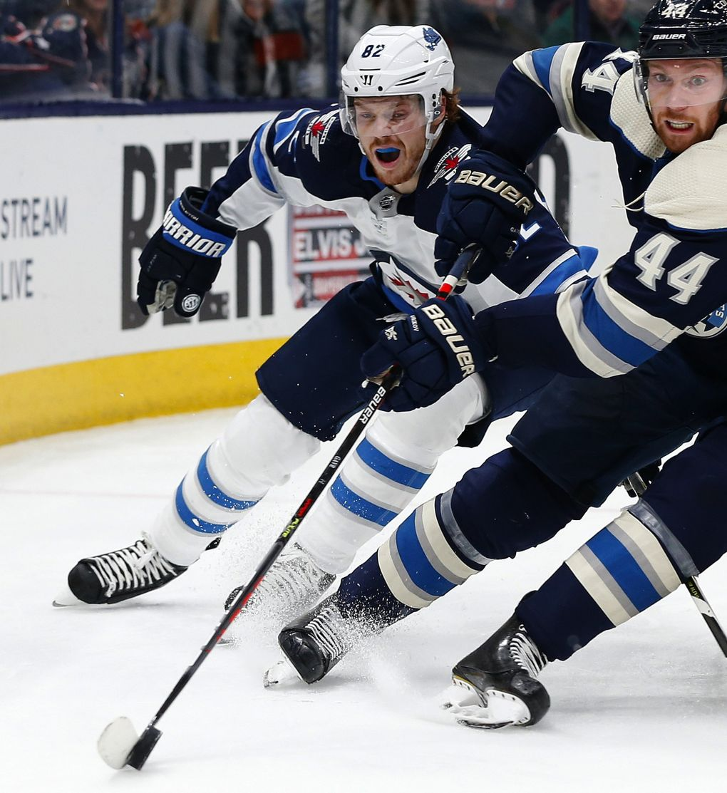 Columbus Blue Jackets' Vladislav Gavrikov, right, of Russia, tries to clear the puck as Winnipeg Jets' Mason Appleton defends during the third period of an NHL hockey game Wednesday, Jan. 22, 2020, in Columbus, Ohio. The Blue Jackets defeated the Jets 4-3. (Jay LaPrete / AP)