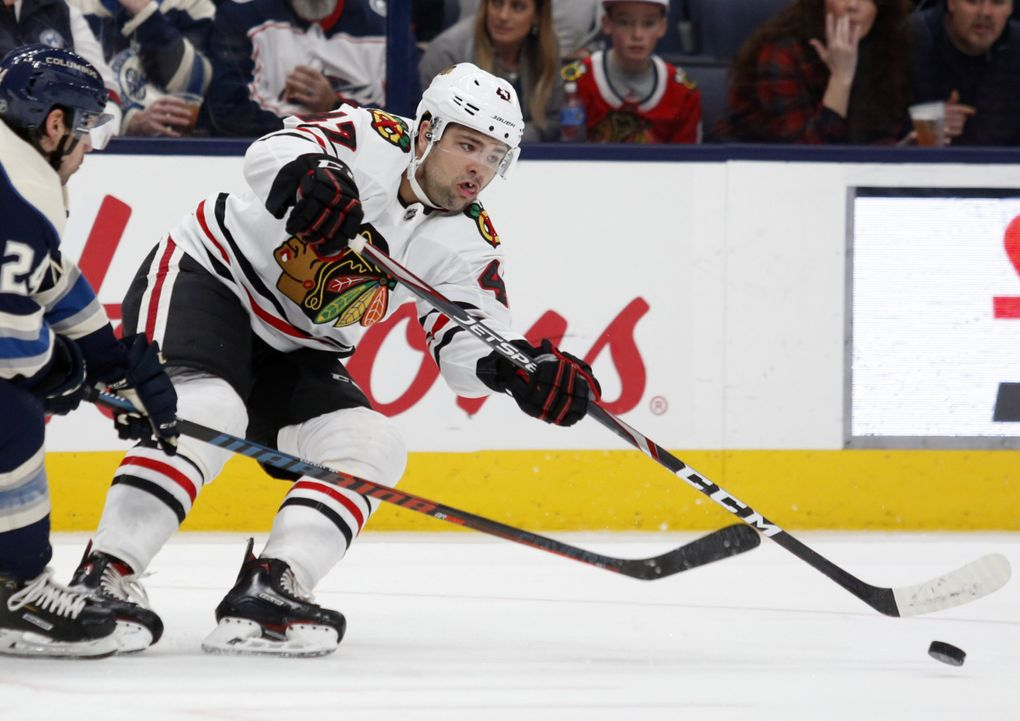 Chicago Blackhawks forward John Quenneville, right, passes the puck in front of Columbus Blue Jackets forward Nathan Gerbe during an NHL hockey game in Columbus, Ohio, Sunday, Dec. 29, 2019. (Paul Vernon / AP)