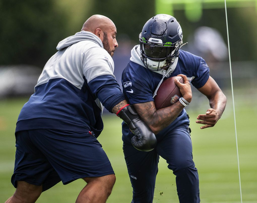 Rashaad Penny runs the boxing drill in which assistant coaches donning boxing gloves provide resistance on the run Wednesday, July 28, 2021 at the VMAC in Renton, WA. (Dean Rutz / The Seattle Times)