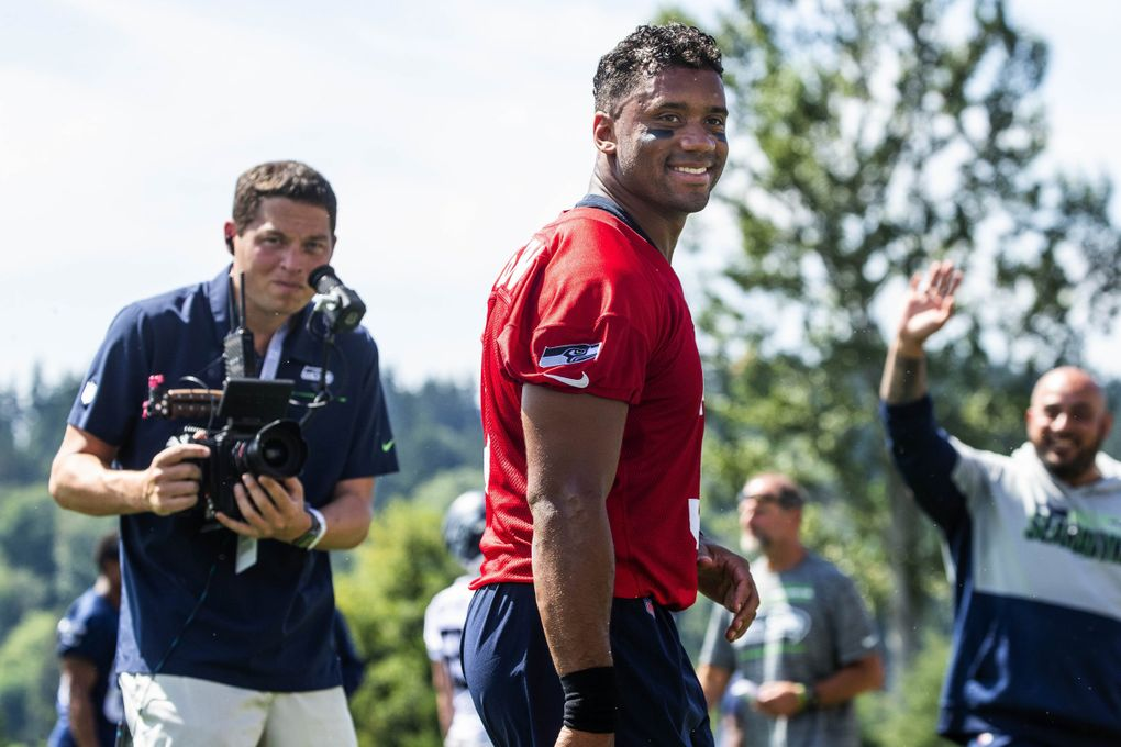 """Russell Wilson smiles as cries of """"Daddy"""" come from his children (Dean Rutz / The Seattle Times)"""
