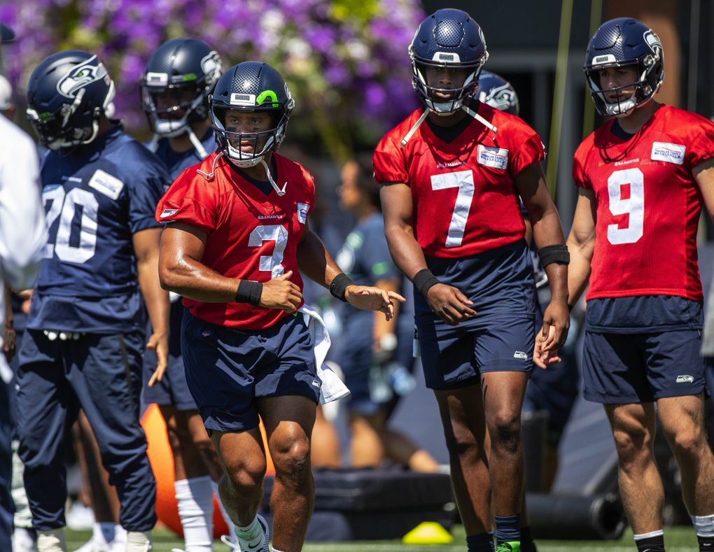 Russell Wilson joins quarterbacks Geno Smith (7) and Danny Etling (9) in warming up for Thursday's practice. (Dean Rutz / The Seattle Times)
