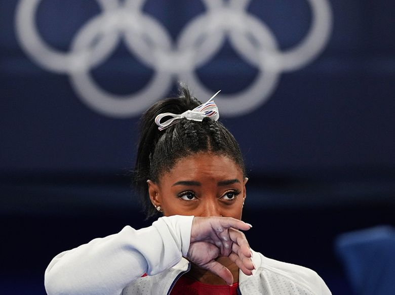 Simone Biles, of the United States, watches gymnasts perform at the 2020 Summer Olympics on Tuesday in Tokyo. Biles says she wasn't in right 'headspace' to compete and withdrew from gymnastics team final to protect herself. (Ashley Landis / The Associated Press)